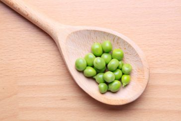 Nutritious looking peas on a wooden spoon.